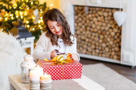 A brunette gilr in front of fur-tree and fireplace with candles and gifts. A surprised girl. A girl dreaming. New year's eve. Christmas eve. Cozy holiday at the fur-tree with lights and gold decor. Stock Photo