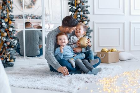 Ein Papa mit seinen beiden Söhnen Zwillinge vor dem Weihnachtsbaum umarmen und Spaß haben. großes Familienkonzept
