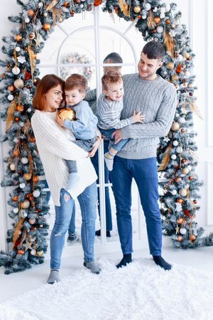 A family of four hugging in front of the christmas tree. love, happiness and big family concept