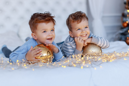 Twin brothers in front of the christmas tree with candles and gifts. New year's eve. Cozy holiday at the fir-tree. love, happiness and big family concept Banque d'images
