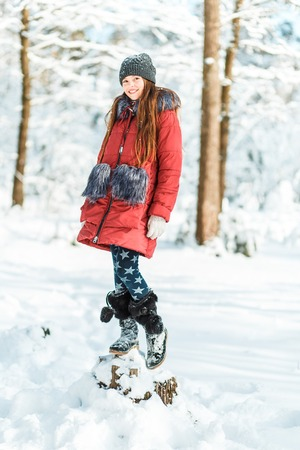 Beautiful teenage girl in a long red down jacket white hat and a scarf having fun outside in a wood with snow in winter Standard-Bild