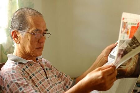 Chinese senior reading newspaper at home. photo