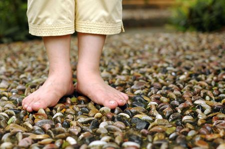 A closeup on foot reflexology walk path at garden. Shallow focus on foot and stone.