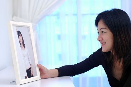 admire: An asian chinese lady admiring her photo at home