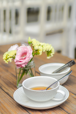 the times on rustic outdoor wood tea table with flower