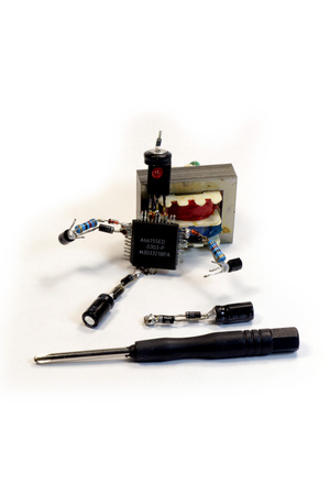 capacitance: The concept - man with a screwdriver engaged in repair of electronic components