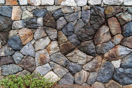 textured wall: Old stone wall texture with green grass Stock Photo