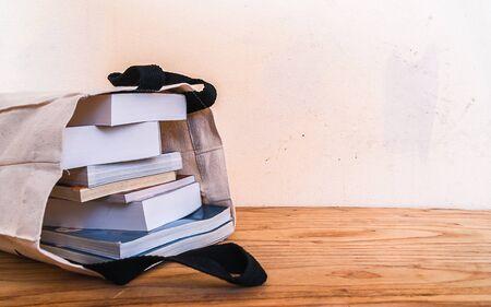 boeken binnen doek zak op houten tafel