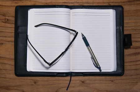writ: Daily planner book in black leather case with glasses and pen on the wooden table Stock Photo