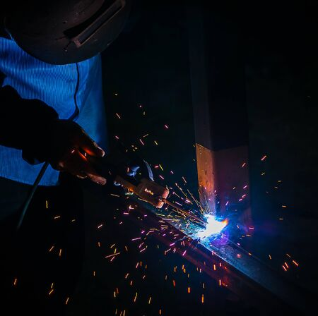 working area: steel welding at industrial, worker on working area with protective mask welding metal