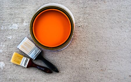 paint brush with open color can on cement floor