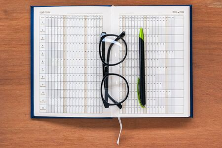 writ: Diary planner book open calendar page with glasses and pen on the wooden desk