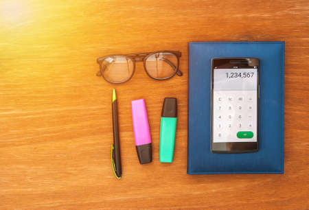 avocation: top view of office desk with smart phone open calculator app