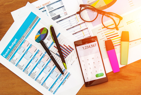 arial view: top view of office desk with data chart and smart phone open calculator app