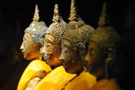 Light on the ancient Buddha statues in the face. Wat Tham Khao Luang Phetchauri, Thailand. photo