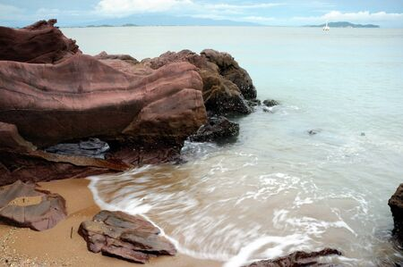 Rocks and sea waves near a pebbly beach in Rayong,Thailand. photo
