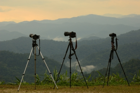 Three camera tripods photographer sunset on the viewpoint rainforest, Thailand  Stock Photo