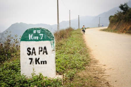 direction sign: 7 kilometer milestone on the highway DT 152 and direction sign to SAPA, north Vietnam. Stock Photo