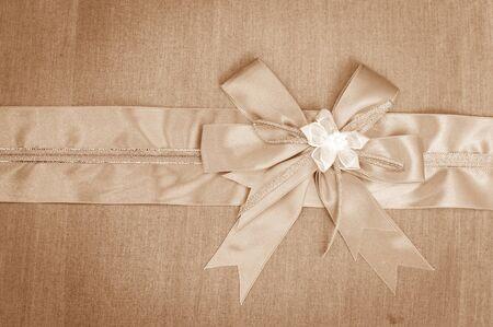 ribbon bow: Abstract ribbon bow on fabric background. Stock Photo