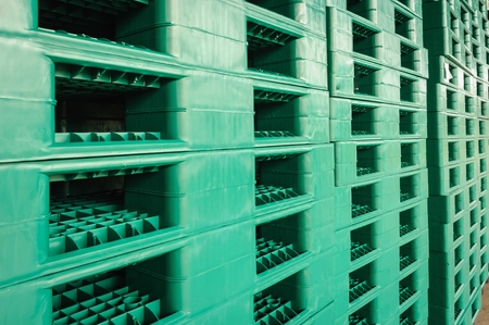 Green plastic pallets in warehouses, sorted and delivered. Archivio Fotografico