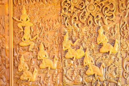 gold teakwood: Wood carving Buddhist temple wall public places of Buddhist worship in Thailand. Stock Photo