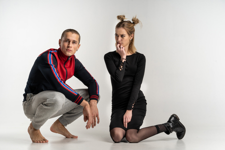 Young beautiful couple sitting on the floor, studio portrait