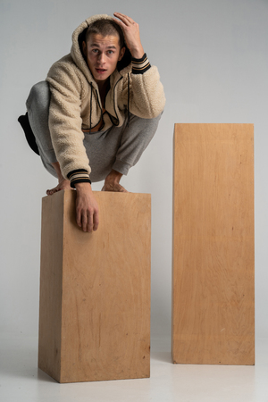 Smart serious young man in sportwear crouched on wood cube and posing