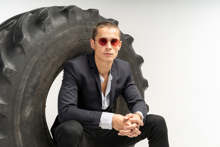 Stylish handsome man in black suit sitting in tire Stock Photo