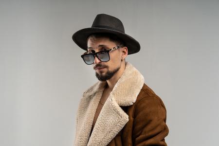 Portrait of an elegant man dressed in brown jacket and black hat