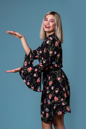 717a108cb3 Image of pretty blonde woman in spring dress showing something big with  hands