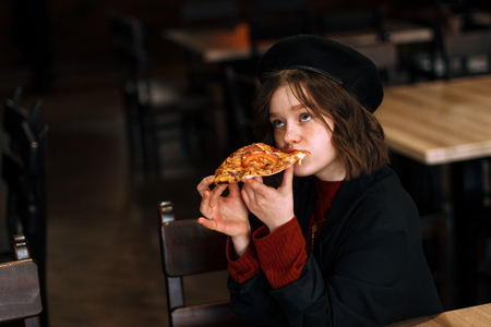 Curly young girl in casual clothes sitting in the cafe Stock Photo