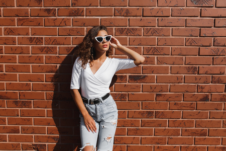 Attarctive elegant young woman hipster in a white sunglasses in a summer denim pants and white t-shirt