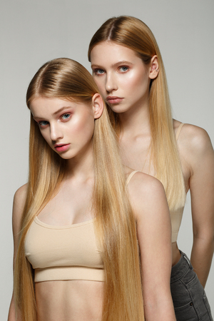 Two sexy attractive twins woman with blonde long hair posing in glamour makeup