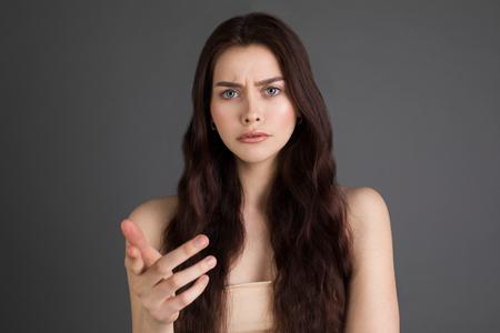 Ritratto di una donna sconvolta, seria e arrabbiata con lunghi capelli castani