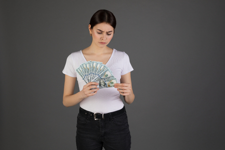Disgusted upset brunette businesswoman in white t-shirt with bunch of money in hand