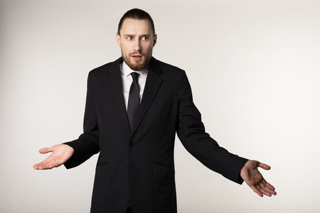 Elegant bearded manager in black suit doing i dont know reaction, isolated on white background