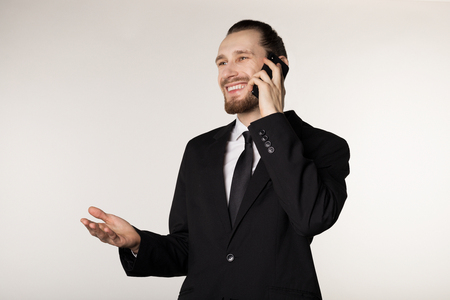 Attractive young busibessman in black suit smilig and talking on the phone with raised palm