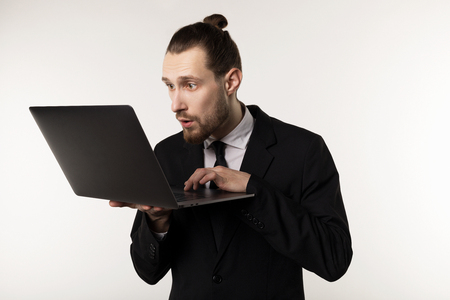Serious bearded businessman or teacher in black suit reading post at notebook Standard-Bild