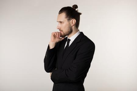 Ritratto di vista laterale di giovane uomo d'affari attraente in vestito nero con l'acconciatura alla moda che tiene la mano sul mento con l'espressione premurosa Archivio Fotografico