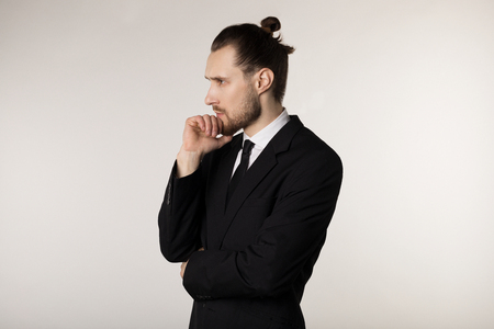 Side view portrait of attractive young businessman in black suit with stylish hairstyle holding hand on chin with thoughtful expression Foto de archivo
