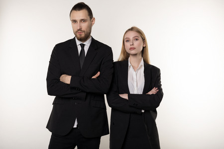 Confident serious businesspeople posing in black suits, standing with crosed hands, looking at camera