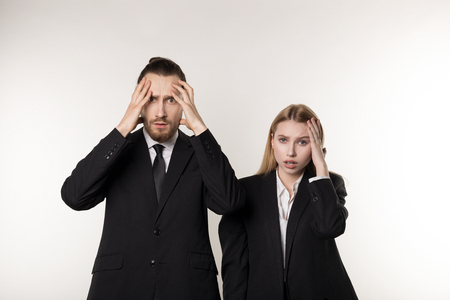 Two young employees in black suits standing with hands on head, laid-off workers after bankruptcy of their company