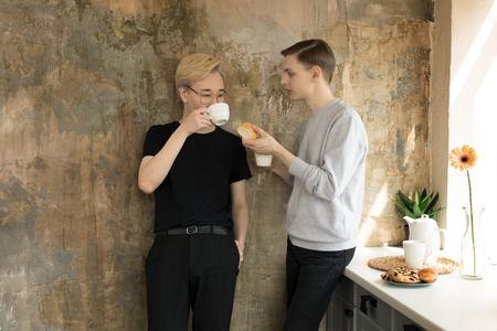 Male partners having food together. International gay couple in casual clothes drinking coffee at home Stock Photo