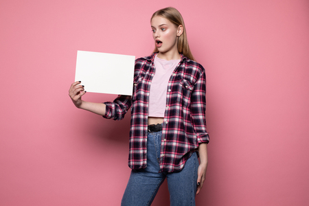 Shocked upset young woman in casual clothes, holding white empty blank for your text 版權商用圖片