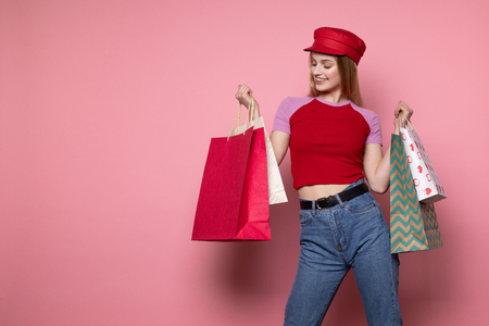 Attractive blonde woman in casual clothes and red hat with colorful shopping bags