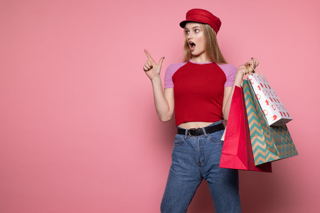 Young beautiful shocked girl in red hat with colorful shopping bags pointing up with finger, looking away Stok Fotoğraf