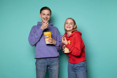 Young happy couple in casual clothes standing isolated over blue background, eating popcorn