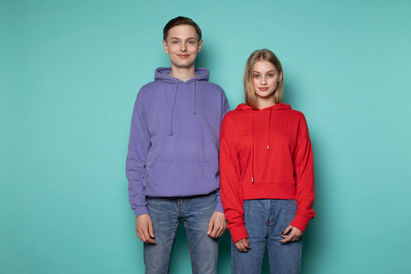 Young beautiful couple in casual clothes standing together against blue wall Imagens