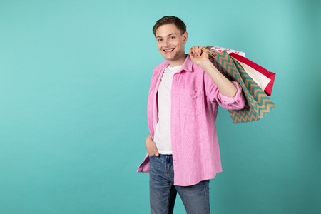 Good looking young man in pink shirt holding colorful shoping bags on the shoulder