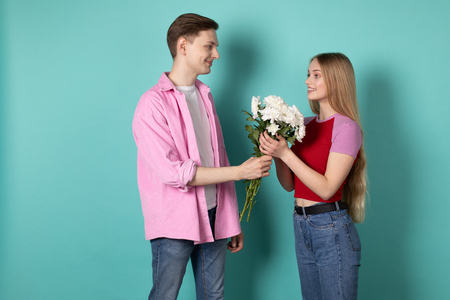 Handsome young man in pink shirt gives a bouquet of white flowers to his beautiful blonde girlfriend Imagens